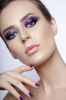 Beauty portrait of a young girl looking at the camera and wearing a fancy make up