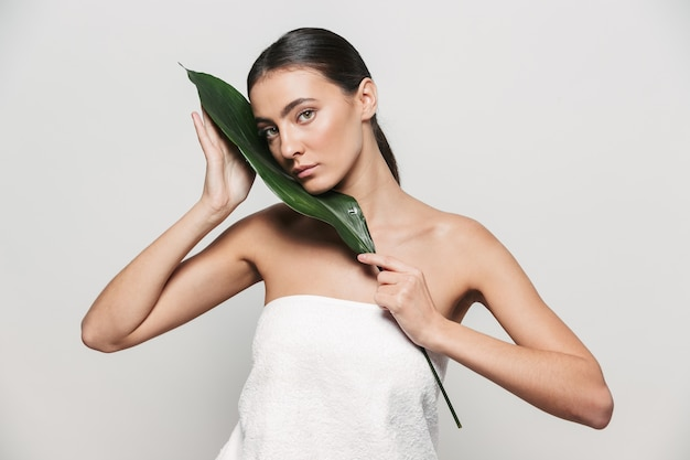 Beauty portrait of a young healthy attractive brunette woman standing isolated, posing with green tropical leaf