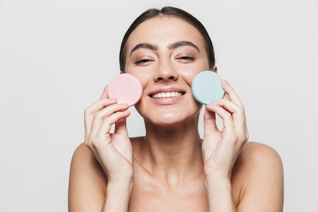 Beauty portrait of a young healthy attractive brunette woman standing isolated, showing makeup sponges