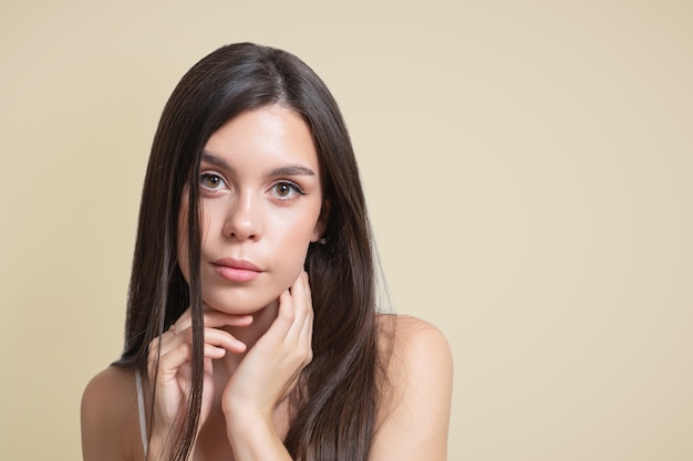 Beauty portrait of a young woman brunette girl on a beige background