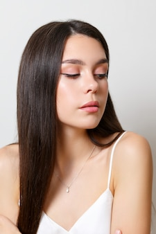 Beauty portrait of a young woman brunette girl on a white background