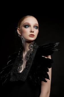 Молодая женщина портрета красоты с воротником черного пера вокруг ее шеи. смелый контрастный макияж на лице девушки