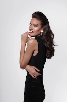Beauty portrait of a young woman with hairstyle and makeup, in black dress, wear luxury jewellery, over white background.