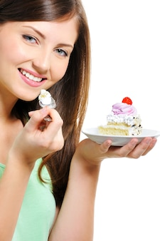 Beauty pretty young female with the cake on plate on white