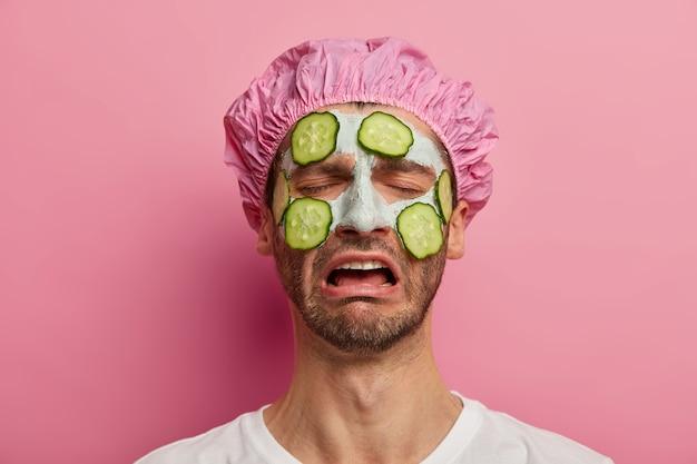 美容法、美容、スキンケアのコンセプト。憂鬱な不満の男は否定的な感情から叫び、バスキャップをかぶって、顔にきゅうりをつけます