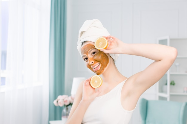 Beauty procedures skin care concept. young woman with brown facial mud clay mask on her face in bathroom, with white towel on head, holding lemon halfs