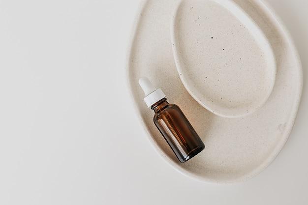 白地にセラミックプレートの美容液、天然薬、エッセンシャルオイル用の美容製品ガラス瓶。コピースペースのある最小限のフラットレイ。