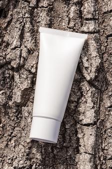 Макет упаковки косметической продукции. органический косметический крем в тюбике на натуральной стене коры дерева. бутылка крема, лосьон, мусс, шампунь для повседневного ухода за кожей.