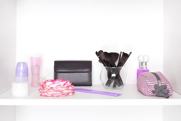 Beauty products and accessories on white shelf inside closet cosmetic and makeup storage
