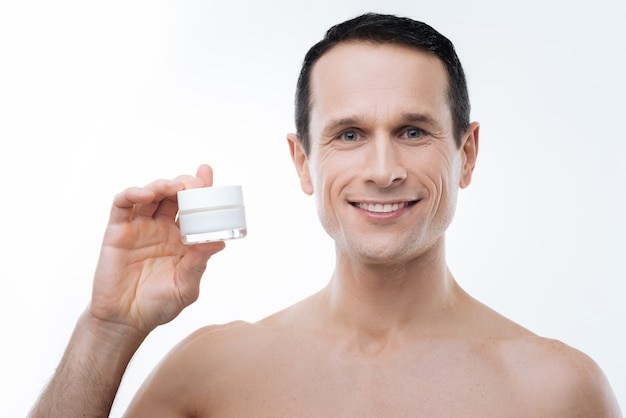 Beauty products. delighted nice good looking man holding a cream bottle and smiling while using facial cosmetics