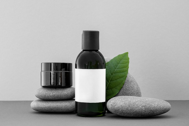 Beauty products in recipients on grey rocks