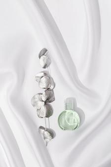 Круглая банка косметики с прозрачным гелем и веткой эвкалипта, окрашенная в серебристый цвет на белой атласной ткани.