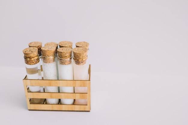 Beauty products test tubes in wooden container on white backdrop