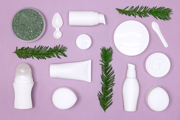 Beauty products with green leaves layout. natural organic skin care cosmetics flat lay
