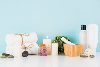 Beauty products with illuminated candles in front of blue wall