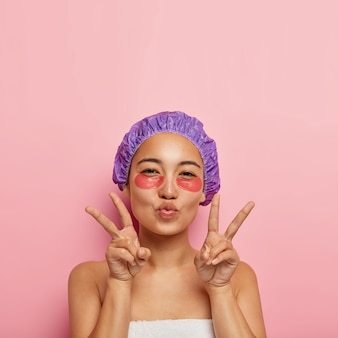 Beauty and rejuvenation concept. pretty korean woman makes peace hand gesture, keeps lips folded, has under eye patches on face, wears purple bath hat, enjoys spa procedures after taking shower