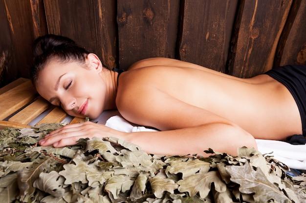 Красота расслабляющая в бане. красивая молодая женщина, расслабляющаяся в бане