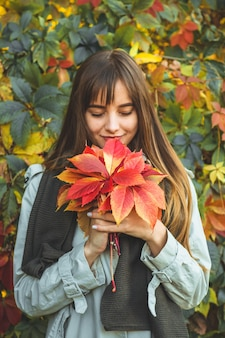 Beauty romantic woman outdoors enjoying nature holding leaves in hands. beautiful autumn model with waving glow hair. sun light on sunset. portrait of romantic female