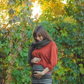 Красота романтичная женщина на открытом воздухе, наслаждаясь природой, держа в руках листья. красивая осенняя модель с развевающимися сияющими волосами. солнечный свет на закате. портрет романтической девушки