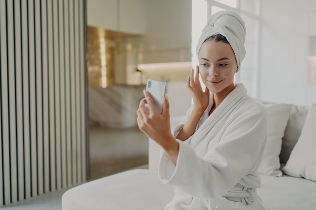 Beauty routine. young gorgeous woman touching her soft healthy skin, applying cosmetic cream while sitting on sofa, female wearing bathrobe and towel on head holding smartphone in front of her face
