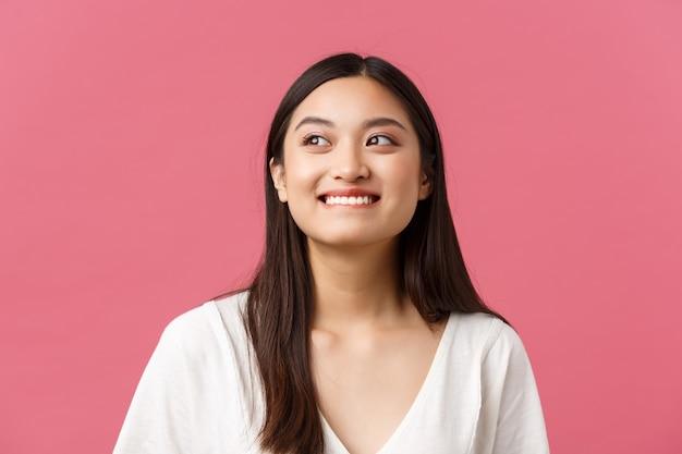 Салон красоты, уход за волосами и концепция рекламы продуктов по уходу за кожей. крупный план соблазнительной и креативной симпатичной азиатской девушки, кусающей губу, улыбающейся, представляющей то, о чем она мечтает, чего она ожидает.