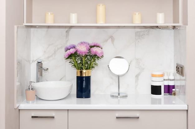 미용실 인테리어. 천연 화장품, 꽃과 함께 테이블에 바디 또는 헤어 케어 제품의 항아리의 집합입니다.