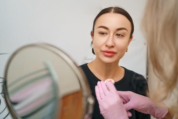 In the beauty salon at the tattoo artist beautiful happy customer.