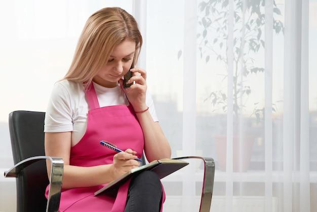 Работник салона красоты разговаривает с клиентом по телефону, договариваясь о встрече