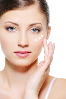 Volto femminile sereno di bellezza con gocce di crema idratante sulla pelle sotto gli occhi