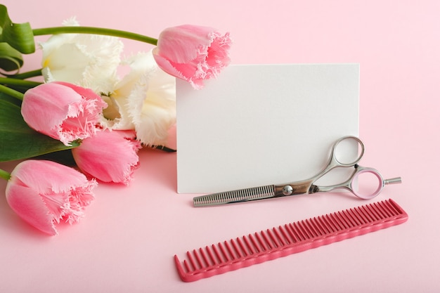 Beauty services. white blank card with space for text, hairdressing scissors comb in bouquet of pink tulips on pink background