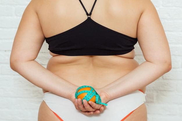 美しさ、形、健康とヘルスケアの女性のコンセプト。測定テープで太りすぎの女の子