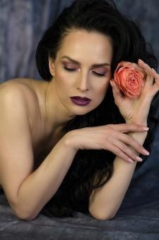 장미를 들고 완벽 한 화장으로 부드러운 갈색 머리 여자의 아름다움 촬영
