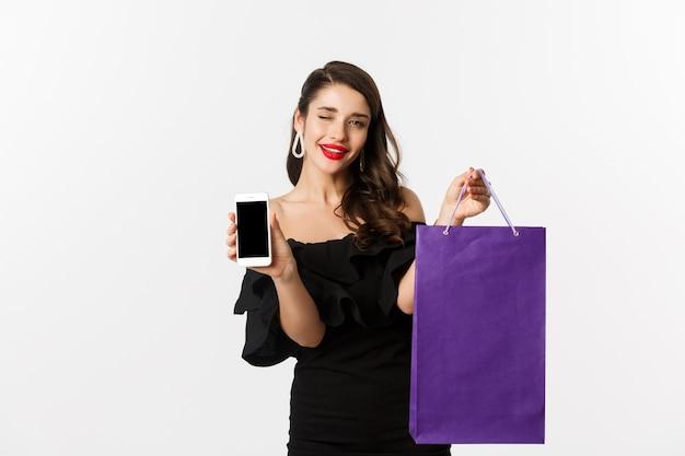 Concetto di bellezza e shopping. donna bella ed elegante che fa l'occhiolino, mostra lo schermo dello smartphone e la borsa, acquista online, in piedi su sfondo bianco.