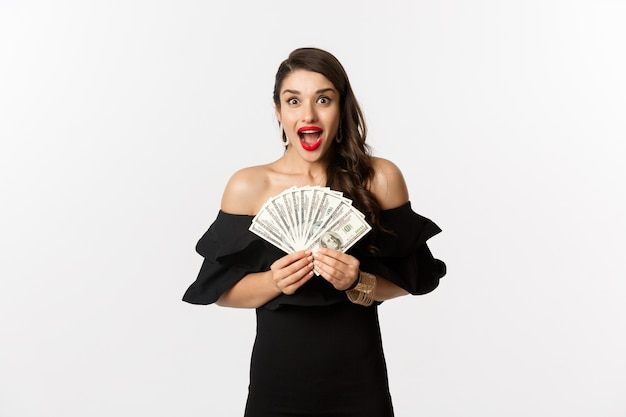 Beauty and shopping concept. excited woman in black dress, showing money prize and staring happy at camera, standing over white background.