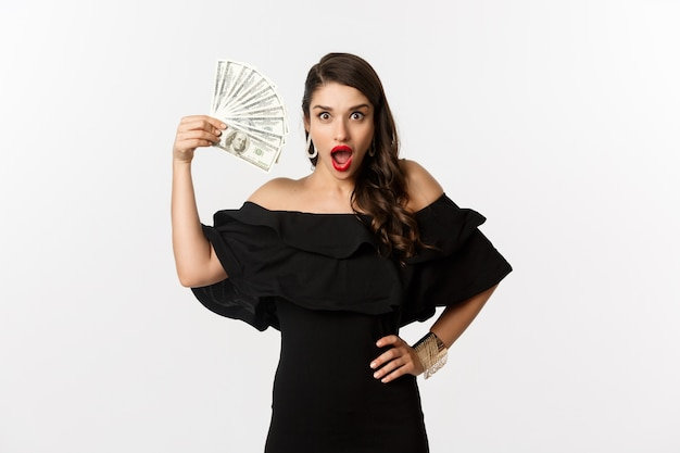 Beauty and shopping concept. fashionable woman with red lips, showing dollars and smiling, standing over white background with money.