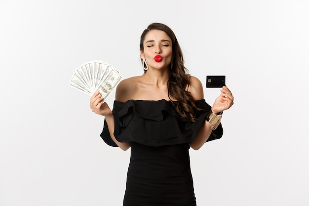 Beauty and shopping concept. pretty glamour woman pucker lips for kiss, showing credit card and dollars, standing over white background.