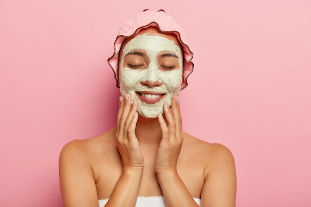 Beauty shot of smiling young ethnic girl applies moisturising mask on face, undergoes facial treatment indoor, stands with bare shouders, wears pink showerhat on head