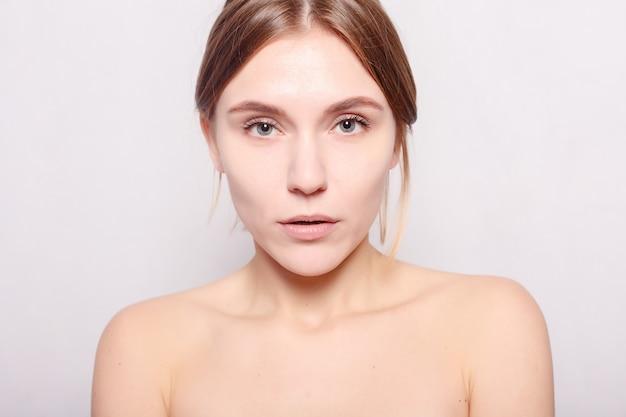 美容、スキンケア、人々のコンセプト-スパウーマン。彼女の顔に触れて入浴後の美しい少女。パーフェクトスキン。スキンケア。彼女の柔らかい肌に触れている彼女の頭にタオルを持つ美女。甘やかす。処理