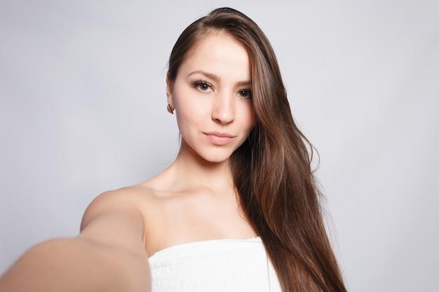 美容、スキンケア、人々のコンセプト-スパウーマン。彼女の顔に触れて入浴後の美しい少女。パーフェクトスキン。スキンケア。自分撮りの時間。自分撮りをしている若い幸せな女性。甘やかす。処理