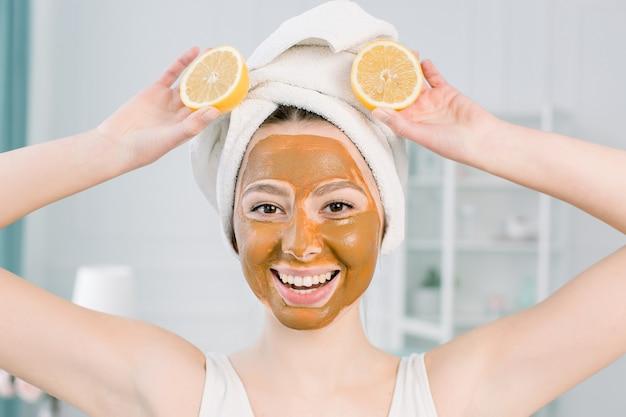 미용 피부 관리 개념. 하얀 수건에 매력적인 백인 여자와 진흙 얼굴 마스크 레몬의 두 반쪽과 재미, 실내 빛 공간에서 촬영