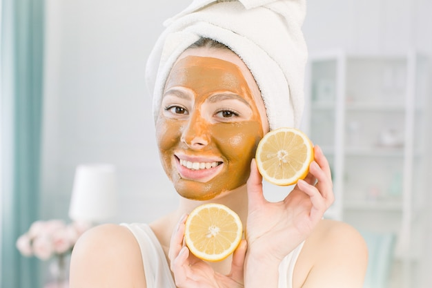 Beauty skin care concept. attractive caucasian woman in white towel and mud facial mask having fun with two halves of lemon, indoor shot in the light space