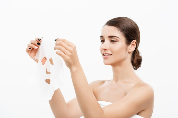 Beauty skin care concept - beautiful caucasian woman applying paper sheet mask on her face white wall.