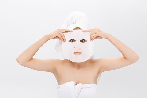 Концепция ухода за кожей красоты - красивая женщина кавказа, применяя маску лист бумаги на белом фоне.
