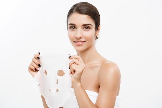 뷰티 스킨 케어 개념-그녀의 얼굴 흰 벽에 종이 시트 마스크를 적용하는 아름 다운 백인 여자.