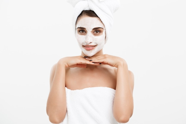 Beauty skin care concept - beautiful caucasian woman face portrait applying cream mask on her facial skin white wall.
