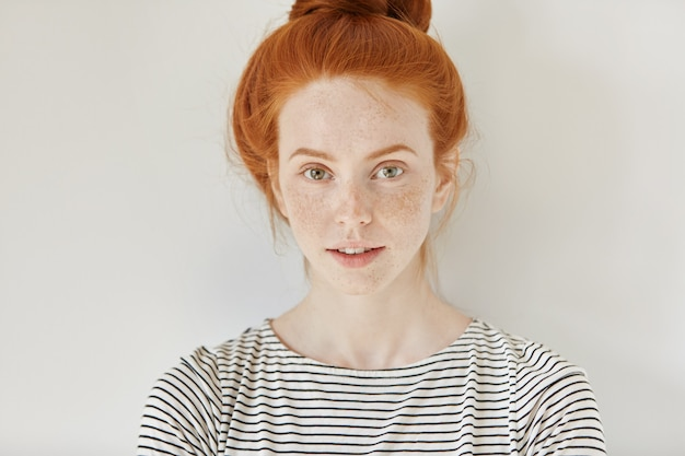Beauty and skin care concept. close up isolated shot of cute stylish young redhead woman with freckles and hair bun looking with charming smile, standing at white wall, wearing sailor shirt