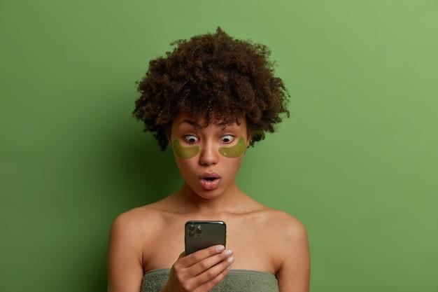 美容、スキンケアのコンセプト。感情的なショックを受けたアフリカ系アメリカ人の女性は、スマートフォンのディスプレイを見つめ、タオルに包まれて立ち、目の下にパッチを適用して腫れを軽減し、インターネットを閲覧します