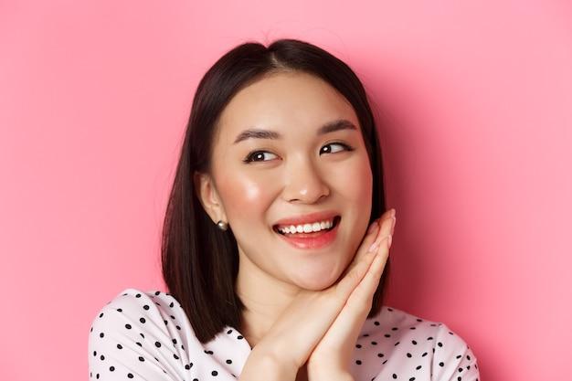 Concetto di bellezza e cura della pelle. colpo in testa di una donna asiatica adorabile e sognante che guarda a sinistra, sorride e immagina, in piedi su sfondo rosa