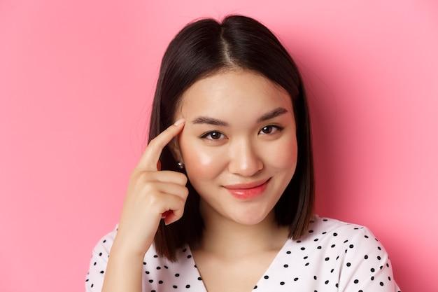 Concetto di bellezza e cura della pelle. colpo in testa di una donna asiatica intelligente che indica la testa e sorride sornione, chiedendo di pensare, in piedi su sfondo rosa
