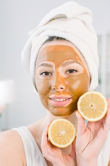 미용 피부 관리 개념. 얼굴에 갈색 진흙 얼굴 마스크와 하얀 수건에 꽤 백인 여자 빛 공간에 그녀의 손에 감귤 류의 과일을 보유하고있다. 스파 절차 및 피부 마스크